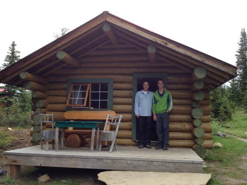 My husband and son on the threshold of our cozy cabin at Mt. Assiniboine Lodge photo - Karen Anderson