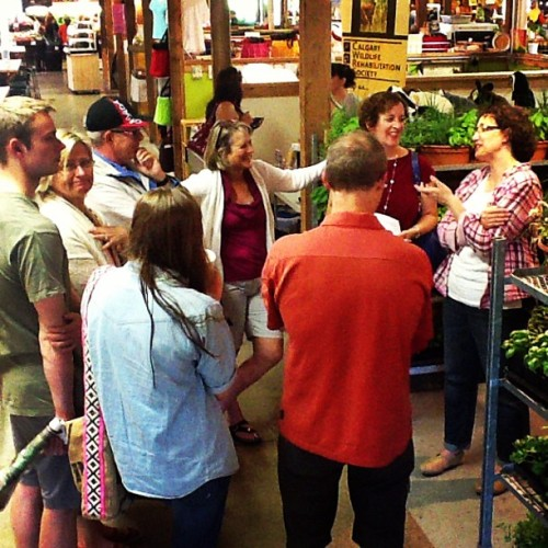 Tracey Aubin of Terra Farms talks to guests and me (in red at back) about growing fresh herbs and how they help us savour our food photo credit and thanks to- Leilani Olynik of Calgary Farmer's Market