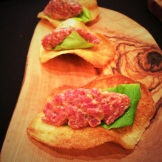 Steak tartare on a crisp potato chip from Cassis Bistro (capers and pepper highlights within) photo - Karen Anderson